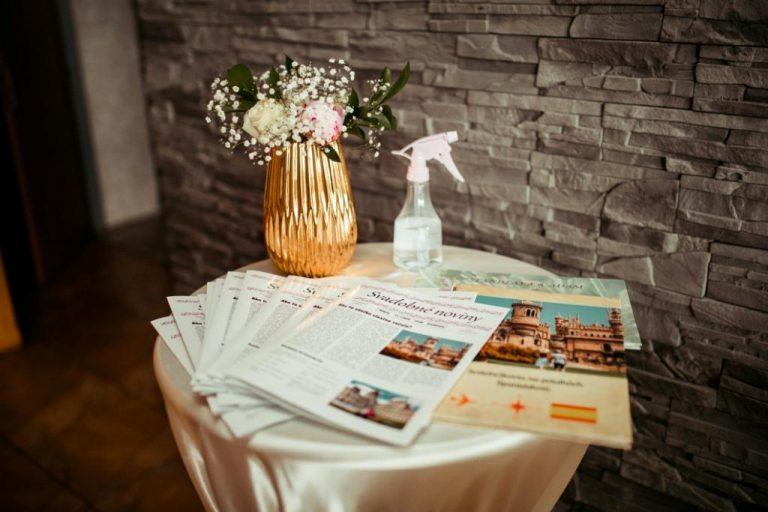 Svadobné noviny určené pre svadobných hostí uložené na sviatočne vyzdobenom stolíku.