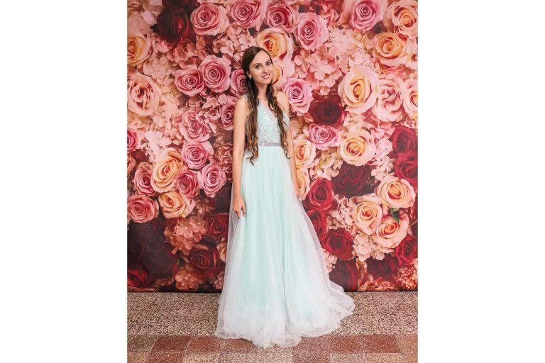 Mladá krásna žena v pastelovo zelených spoločenských šatách pred kvetinovým vynilovým fotopozadím rozmeru 290x230 cm