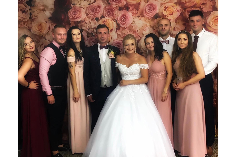 Nevesta so ženíchom a ich 7 priateľov v spoločenských šatách pred kvetinovým vynilovým fotopozadím rozmeru 290x230 cm