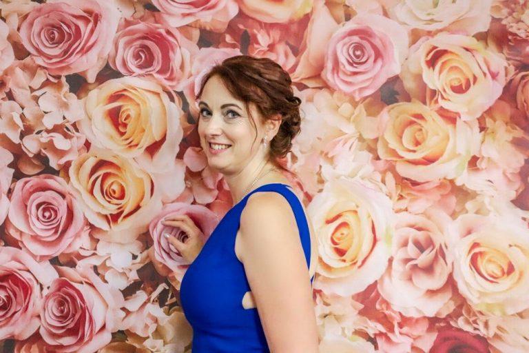 Krásna žena v strednom veku v kráľovsky modrých spoločenských šatách pred kvetinovým vynilovým fotopozadím rozmeru 290x230 cm